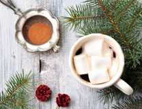 Chocolate or cocoa drink with marshmallows in a Christmas cup on the background of spruce Royalty Free Stock Images