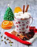 Chocolate or cocoa drink with marshmallows and cinnamon in a Christmas cup with cinnamon on gray wooden background royalty free stock image
