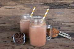 Chocolate and cocoa mixed with milk smoothies on wooden floor. royalty free stock photography