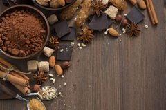 Chocolate, cocoa, nuts and spices on wooden background, top view Royalty Free Stock Image