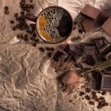 Chocolate, cocoa powder and coffee cup. Large pieces of dark chocolate, cocoa powder and coffee cup on craft paper stock images