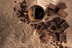 Chocolate, cocoa powder and coffee cup. Large pieces of dark chocolate, cocoa powder and coffee cup on craft paper. top view. copy space royalty free stock image