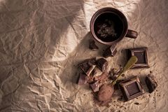 Chocolate, cocoa powder and coffee cup. Large pieces of dark chocolate, cocoa powder and coffee cup on craft paper. top view. copy space royalty free stock photos