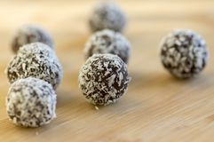 Chocolate coconut balls decorated with shredded coconut on wooden bamboo table royalty free stock photography