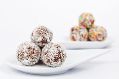 Chocolate and coconut balls on a white plate. On white Royalty Free Stock Image