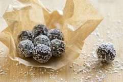 Chocolate coconut balls wrapped in baking paper decorated with shredded coconut on wooden bamboo table. Very tasty Stock Photography