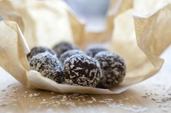 Chocolate coconut balls wrapped in baking paper decorated with shredded coconut on wooden bamboo table. Delicious cookies Stock Photos
