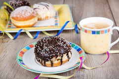 Chocolate and coconut donuts with carnival decoration. Royalty Free Stock Image