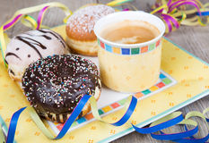 Chocolate and coconut donuts with carnival decoration. Royalty Free Stock Images
