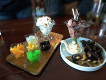 Chocolate and Coconut ice-cream with toping.Cake on wooden table royalty free stock photography