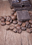 Chocolate and coffee. Raw coffee beans and chocolate on old wooden plank Royalty Free Stock Image