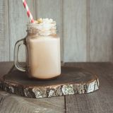 Chocolate coffee milkshake with whipped cream served in glass mason jar on gray wooden background. Summer drink. Square image. Chocolate coffee milkshake with Royalty Free Stock Photo