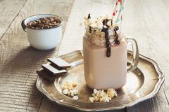 Chocolate coffee milkshake with whipped cream served in glass mason jar on vintage wooden background. Sweet drink. Chocolate coffee milkshake with whipped cream Stock Image