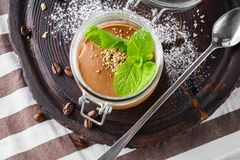 Chocolate coffee pudding or mousse with halvah, mint in a jar stock images