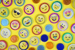 Chocolate coins. Top view photo of chocolate coins with various expressions, pop art style, on a yellow background
