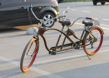A tandem bicycle with scarlet wheel rims is parked in a parking lot in the evening sun. A chocolate-colored tandem bicycle with scarlet wheels is parked in a Stock Images