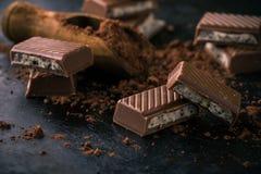 Chocolate con el relleno cremoso en tablero negro con cacao Fotos de archivo libres de regalías
