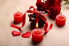 Chocolate con la cinta, las rosas y las velas rojas Fotos de archivo libres de regalías