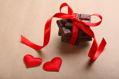 Chocolate con la cinta roja y los pequeños corazones Foto de archivo libre de regalías