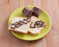 Chocolate con pan en una tarjeta de madera Imagen de archivo