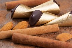 Chocolate cones with sticks of cinnamon and nuts. Chocolate cones with cinnamon sticks and almonds and walnuts Stock Photo