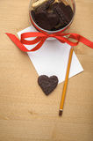 Chocolate cookie-heart on a piece of paper with pencil Stock Images
