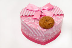 Chocolate cookie and heart shaped pink box with bow Royalty Free Stock Images