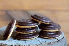 Sweet biscuits pile on a wooden background. Round biscuits in chocolate glaze icing made with cocoa powder. Closeup Royalty Free Stock Images