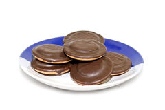 Chocolate cookies. A pile of chocolate cookies on the plate, isolated on white background Stock Photography