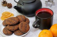 Chocolate cookies and black tea utensils. Cup and teapot. Dried orange slices. Tea scene.  stock photos