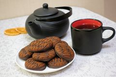 Chocolate cookies and black tea utensils. Cup and teapot. Dried orange slices. Tea scene.  royalty free stock photo