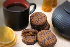 Chocolate cookies and black tea utensils. Cup and teapot. Dried orange slices. Tea scene.  royalty free stock photography