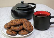 Chocolate cookies and black tea utensils. Cup and teapot. Tea scene.  stock photos