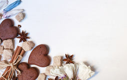 Chocolate cookies, brown sugar, anisetree and cinnamon on white. Wooden background Royalty Free Stock Image