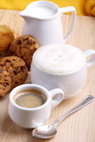 Chocolate cookies with coffee and cappuccino. Cup of coffee with milk and cappuccino on table in chestnut wood Royalty Free Stock Photography
