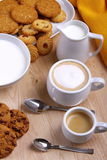 Chocolate cookies with coffee and cappuccino and small pastries. Cup of coffee with milk and cappuccino on table in chestnut wood Royalty Free Stock Photos