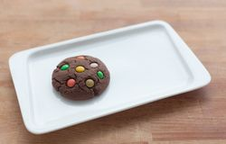 Chocolate cookies with colorful candy on a plate Royalty Free Stock Images