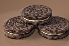 Chocolate cookies with creme filing. On a brown plate Stock Image