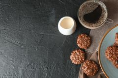 Chocolate cookies, cup of coffee and milk on black table royalty free stock photography