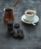 Chocolate cookies with cup and pot of coffee, dark Royalty Free Stock Images