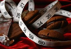 Chocolate Cookies Dieting Temptation. Image of 3 chocolate cookies wrapped in a tape measure, conceptual temptation stock image