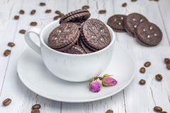 Chocolate cookies with filling in the cup. On the wooden table Stock Photography