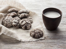 Chocolate cookies on a linen a napkin with milk in ceramic cup on a light wooden background. Royalty Free Stock Images