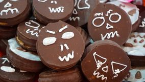 Chocolate cookies. Many cookies covered with chocolate with some faces painted in it with a sugar pasta, angry and sad faces over some baked cookies Stock Images