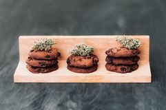 Chocolate cookies with marijuana. Sweets with cannabis. Cannabis buds on a black background. stock image