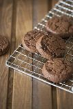 Chocolate cookies at metal grill on wood background stock images