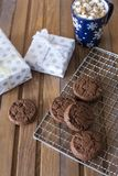 Chocolate cookies at metal grill, with napkin, cup of chocolate and present on wood background stock image