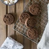 Chocolate cookies at metal grill, with napkin and cup near on wood background stock images