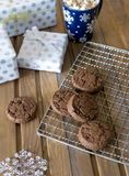 Chocolate cookies at metal grill, with napkin and present on wood background stock photos