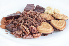 Chocolate,cookies and nuts lying at the white plate. Isolated objects Royalty Free Stock Photos